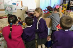 P2 children from KPS helping make hampers at The Beacon